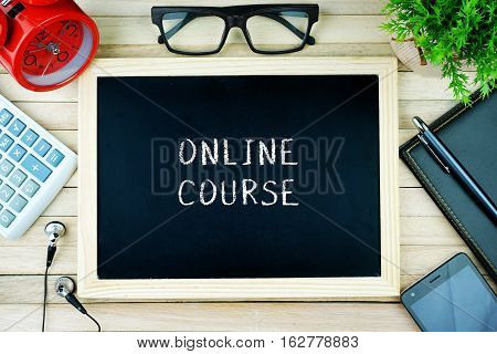 Top view of earphone, calculator, alarm clock, spectacle, notebook, pen, smartphone and chalkboard written with ONLINE COURSE.