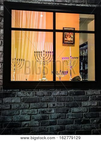 TEL AVIV ISRAEL - DECEMBER 22 2016: Showcase of Judaic store before the Hanukkah holiday with exposed different sizes and designs menorahs (traditional candelabra)