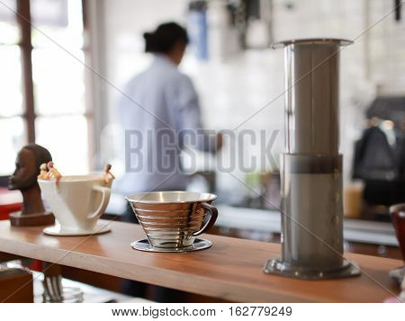 Coffee cup in couture with blurred barista background.