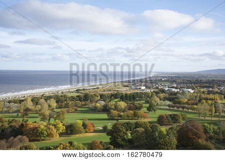 The town of Abergele in Wales UK overlooking the ocean coastline featuring the towns of Aberegle Pensarn Rhyl and Kinmel bay in the distance the foreground a gold course in Autumn with blue sky and clouds.