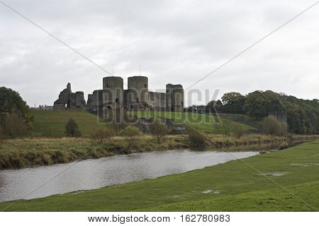 Rhuddlan Castle, North Wales ,UK, a Norman castle constructed in the thirteenth century by the river Clwyd, surrounded by fields and trees in autumn