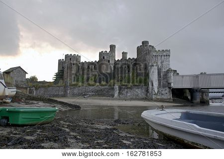 Conwy Castle south side showing stormy weather, sand bank, and river conwy with boats in the foreground