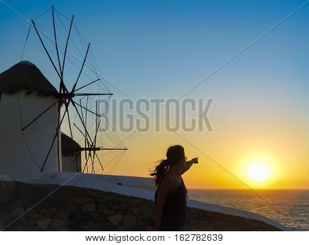 Tourist Enjoying The Sunset At The Windmills In Mykonos