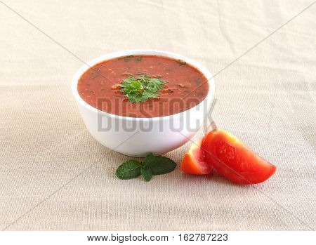 Healthy raw vegetarian food tomato curry in a bowl and slices of tomato.