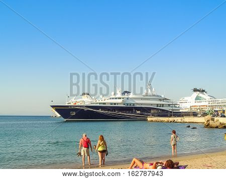 Tourists And A Giant Yacht At The Mandraki Port