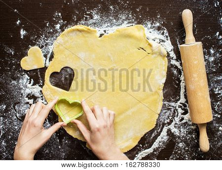Woman's hands made from the dough heart. The symbols of protection, warmth and comfort. Baking lovers on Valentine's Day