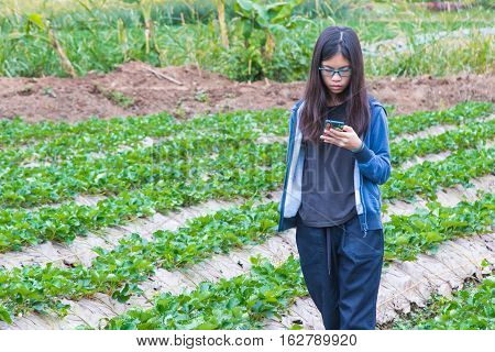 young asian teenager using mobile phone technology outdoor in strawberry field showing no boundary in learning