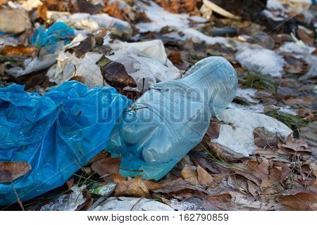 Pile of plastic bags and other refined petroleum products dumped in landfill. Garbage heap gives infiltrate into groundwater. Waste sorting is required. Blue plastic bottle,