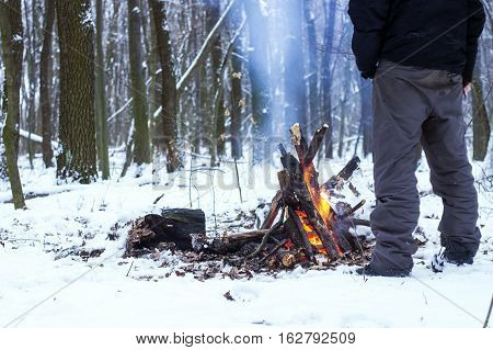 Man Warming His Hands Around A Campfire In The Forest