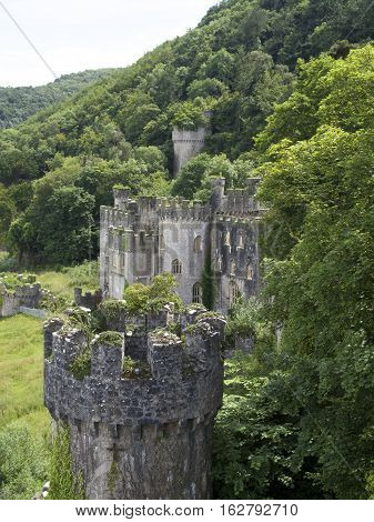 Gwrych Castle In Wales Uk Surrounded Bu Trees And Foliage On Hill Side.