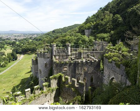 Gwrych Castle In Wales Uk Surrounded By Trees And Foliage On Hill Side - Full Ruins Overlooking The