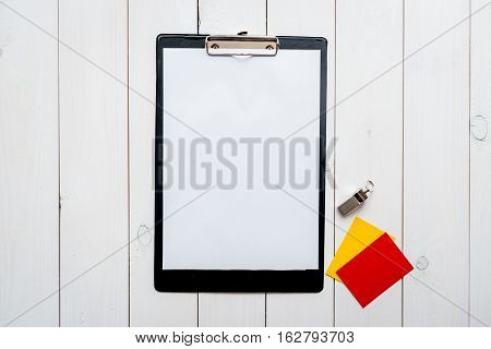 refereeing in the sport on wooden background top view mock up blank sports clipboard and whistle