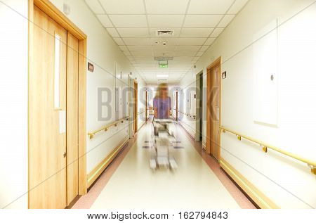 A blurred figure of nurse, coming down a well lit hospital corridor, pushing equipment.