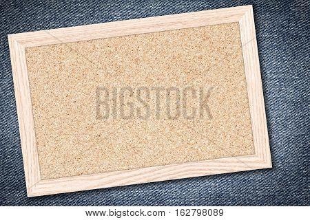 Cork board or Empty bulletin board with a wooden frame on denim jeans background with copy space for text or image.