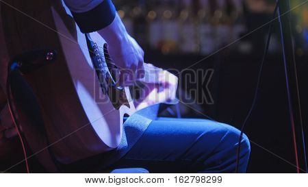 Guitarist plays concert acoustic guitar in night club, telephoto