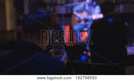 Girl in night club drink coffee during rock guitarist at scene plays guitar for spectators, telephoto