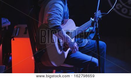 Guitarist - young man - plays concert acoustic guitar in night club, telephoto
