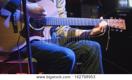 Guitarist plays acoustic guitar and sings microphone in night club, blue lights, close up, telephoto