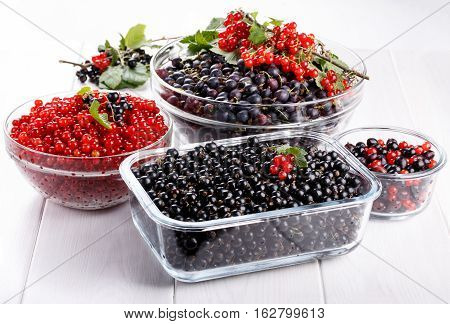 Black gooseberries blackcurrants and redcurrants. Fresh summer berries in a glass bowl on white.