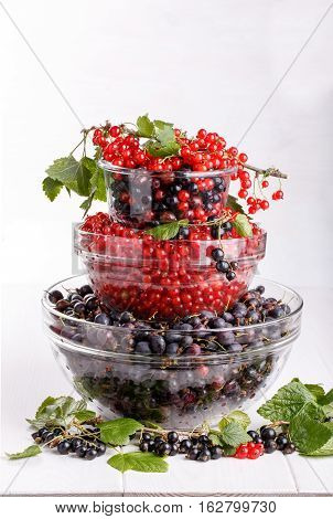 Stack of three glass bowls with fresh summer berries on white. Black gooseberries blackcurrants and redcurrants.