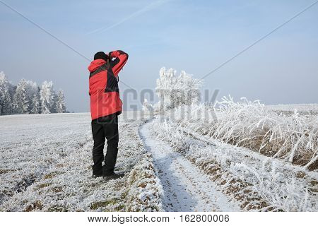 Winter landscape and snow wrapped trees in Sumava Czech republic. Photographer with cap standing in a meadow and photographing landscapes.in the Sumava. South Bohemia.