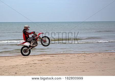 Motorbiking on one wheel at the seaside