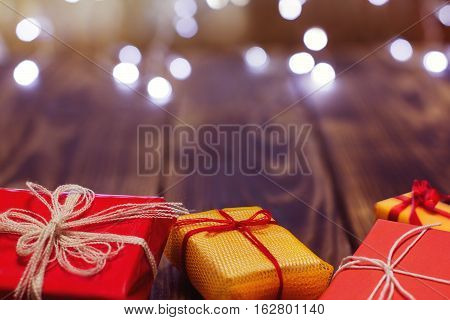 gifts in different colorful packages on a wooden background with bokeh