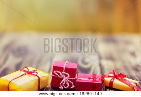 gifts in different packages on a yellow and brown wooden background
