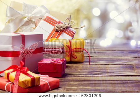 gifts in different packages on a wooden background with bokeh