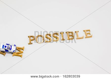 Changing the word impossible to possible with crashing car toy. Concept of positive attitude