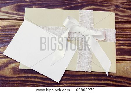 envelope with white ribbon and white blank card on a wooden background
