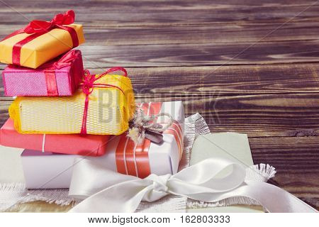 pyramid from gifts in a different colorful packages on a wooden background