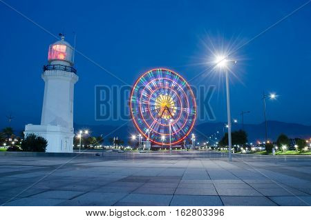 Night view of ferris wheel and old lighthouse located in Amusement Park at city seafront in Batumi Georgia