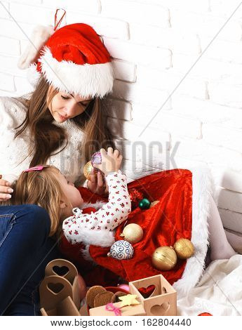 young cute little blonde girl in christmas red dress and coat lying on her mothers lap in xmas hat and long brunette hair and holding new year colorful balls on white brick wall background