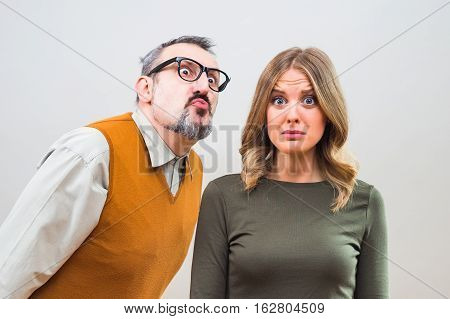 Nerdy man is trying to get beautiful woman's attention but she is not interested and desperately thinking the way to escape.