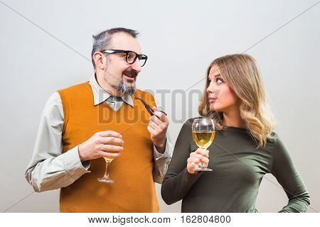 Self confident nerdy man is trying to get beautiful woman's attention but she is not interested.