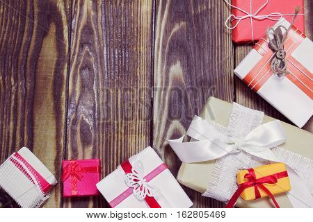gifts in a different colorful packages on a wooden background