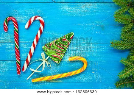 Christmas treats: colorful lollipops in the form of spruce candy canes and green spruce branches on a blue wooden board . Celebratory theme.