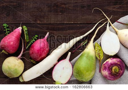 Several kinds of radish (daikon Chinese red green) on a wooden table. Useful vitamins ingredient for salads. The top view.