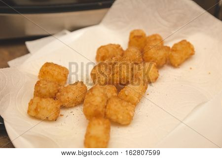 Tater tots made at home, sprinkled with salt and pepper, on paper towels in kitchen setting.