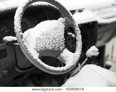 Power steering wheel and a driver seat in particular focus, car interior covered with snow