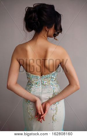 Beautiful woman in elegant evening dress with naked back. Professional make-up and hairstyle. Perfect skin. Fashion photo.