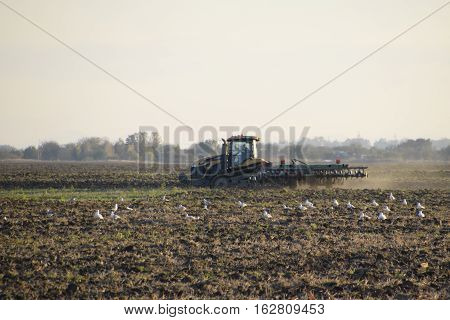 Tractor Plowing Plow The Field. Tilling The Soil In The Fall After Harvest. The End Of The Season
