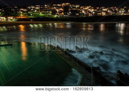 Sydney, Australia - May 28, 2016: Nightfall at Bronte Baths, Sydney, New South Wales, Australia. High resolution image showing long exposure of tidal wave movements throwing up mists of water droplets.
