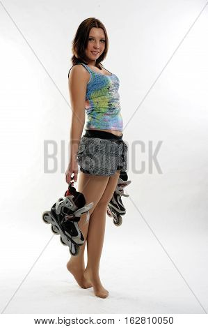Young attractive woman with roller skates relaxing over white background