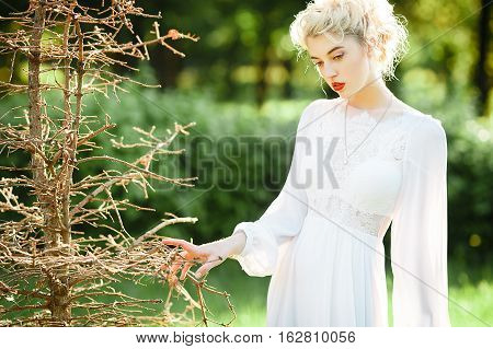 Fine art outdoor portrait of beautiful young blonde woman in a white dress.