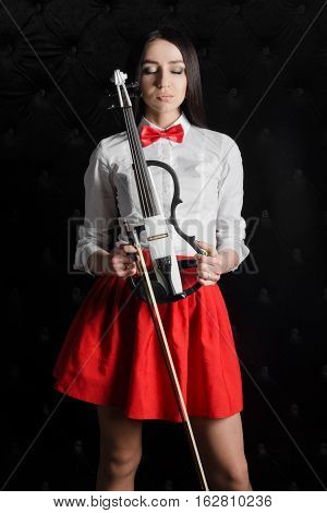 Young woman portrait with a violin. In white shirt with a bow tie. Hands holding a violin. Closed eyes
