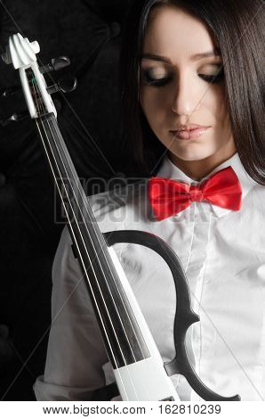 Portrait of a beautiful young woman with a violin. In white shirt with a red bow tie. Bowed his head