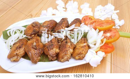Marinated chicken wings fried has decorate are onions tomato on the banana leaf in plate and background is canna flower.