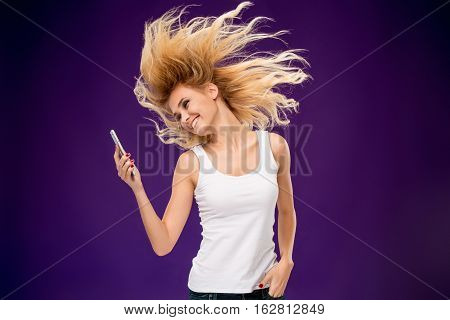 Portrait of beautiful smiling girl making selfie with modern cell phone in hands on lilac background.